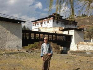 Photo of Francoise Pommaret in front of a Tibetan monastery, wearing traditional dress