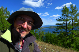 Photo of Jeremy Tredinnick outdoors with blue sky hills and lakes