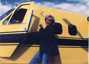Photo of Masha Nordbye, Odyssey author, standing next to a yellow aircraft